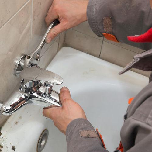 A Plumber Repairs a Faucet.