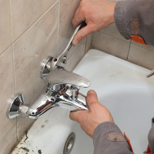 A Plumber Adjusts a Bathtub Faucet.