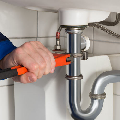 A Plumber Tightens a Pipe Under a Sink.