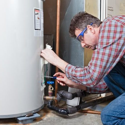 A Picture of a Man Working On a Water Heater.
