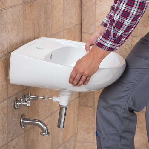 A Picture of a Plumber Installing a Sink.