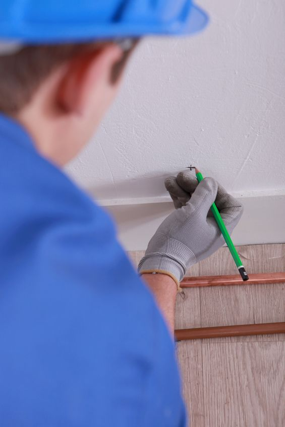 A Picture of a Plumber Using a Pencil To Mark the Spot Where Pipes Will Be Installed.